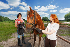 Young couple preparing for horseback ride at farm Stock Photography