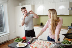 Young couple preparing the pizza in the kitchen royalty free stock photo