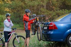 Young Couple Unmounting Mountain Bikes from Bike Rack on the Car. Adventure and Family Travel Concept. Royalty Free Stock Images