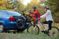 Young Couple Unmounting Mountain Bikes from Bike Rack on the Car. Adventure and Family Travel Concept. Stock Images