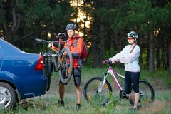 Young Couple Unmounting Mountain Bikes from Bike Rack on the Car. Adventure and Family Travel Concept. Royalty Free Stock Photography