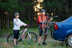 Young Couple Unmounting Mountain Bikes from Bike Rack on the Car. Adventure and Family Travel Concept. Young Couple Preparing for Riding the Mountain Bikes in Stock Photography