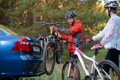 Young Couple Unmounting Mountain Bikes from Bike Rack on the Car. Adventure and Family Travel Concept. Royalty Free Stock Photos