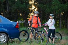 Young Couple Unmounting Mountain Bikes from Bike Rack on the Car. Adventure and Family Travel Concept. Young Couple Preparing for Riding the Mountain Bikes in Royalty Free Stock Image