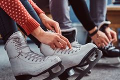 Young couple preparing to a skating. Close-up photo of their hands tying shoelaces of ice hockey skates in the locker. Young couple preparing to a skating. Close stock photo