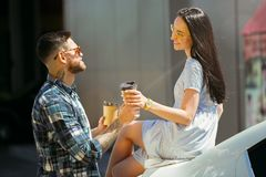 Young couple preparing for vacation trip on the car in sunny day. Woman and men drinking coffee and ready for going to sea or ocean. Concept of relationship royalty free stock photos