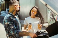 Young couple preparing for vacation trip on the car in sunny day. Woman and men drinking coffee and ready for going to sea or ocean. Concept of relationship stock photo