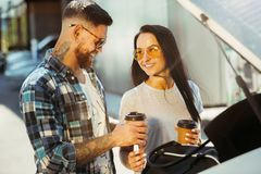 Young couple preparing for vacation trip on the car in sunny day. Woman and men drinking coffee and ready for going to sea or ocean. Concept of relationship stock images