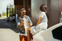 Young couple preparing for vacation trip on the car in sunny day. Woman and men drinking coffee and ready for going to sea or ocean. Concept of relationship stock image