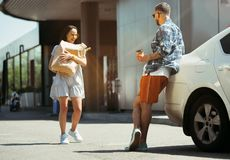 Young couple preparing for vacation trip on the car in sunny day. Woman and men shopping and ready for going to sea, riverside or ocean. Concept of royalty free stock photo