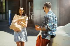 Young couple preparing for vacation trip on the car in sunny day. Woman and men shopping and ready for going to sea, riverside or ocean. Concept of stock image