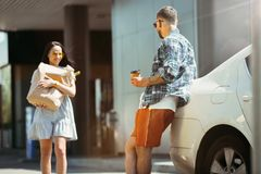 Young couple preparing for vacation trip on the car in sunny day. Woman and men shopping and ready for going to sea, riverside or ocean. Concept of stock photography