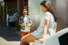 Young couple preparing for vacation trip on the car in sunny day. Woman and men shopping and ready for going to sea, riverside or ocean. Concept of stock images