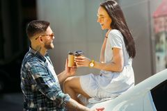 Young couple preparing for vacation trip on the car in sunny day. Woman and men drinking coffee and ready for going to sea or ocean. Concept of relationship royalty free stock image