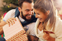 Young couple with present over Christmas tree Royalty Free Stock Photography