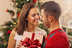 Young couple with present over Christmas tree Stock Photography