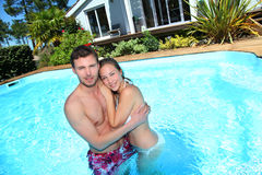 Young couple in private swimming pool enjoying summer. Young couple in private swimming pool Royalty Free Stock Photos