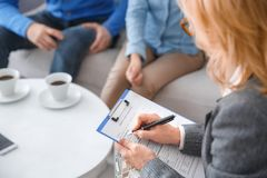 Young couple with psychologist family therapy therapist close-up filfilling medical form. Young couple men and women with middle-aged female psychologist family Stock Photography