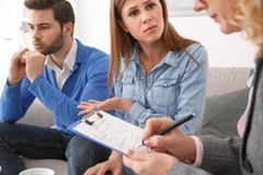 Young couple with psychologist family therapy therapist taking notes. Young couple men and women with middle-aged female psychologist family therapy sitting on royalty free stock photos