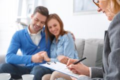 Young couple with psychologist family therapy therapist writing diagnosis close-up. Young couple men and women with middle-aged female psychologist family Stock Photos