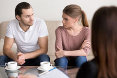 Young couple at psychologist, looking at each other with hate Stock Images