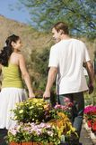 Young couple pulling cart with potted flowers Stock Photo