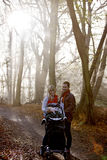 A young couple pushing a stroller in the park, talking Royalty Free Stock Photos
