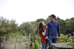 A young couple pushing a wheelbarrow on an allotment Royalty Free Stock Photography