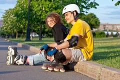 Young couple put on inline skates Stock Photos