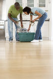 Young couple putting glass jars, cans and newspapers into recycling bin in kitchen, low angle view Stock Image