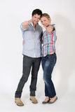 Young couple putting thumbs up isolated. Young couple showing thumbs up on white background Royalty Free Stock Photos