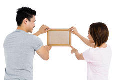 Young couple putting up picture frame Royalty Free Stock Photo