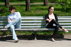 Young couple in quarrel. Sitting on bench in park Royalty Free Stock Photos