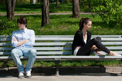 Young couple in quarrel. Sitting on bench in park Stock Photography