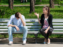 Young couple in quarrel. Sitting on bench in park Royalty Free Stock Image
