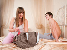Young couple in quarrel. girl collects things Stock Photos