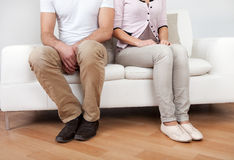 Young couple in quarrel at home. Sitting on the couch Stock Image