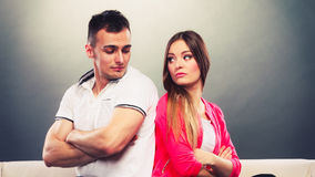 Young couple after quarrel sitting on sofa back to back. Bad relationship concept. Man and women in disagreement. Young couple after quarrel sitting on sofa back Royalty Free Stock Photography