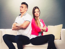 Young couple after quarrel sitting on sofa back to back. Bad relationship concept. Man and women in disagreement. Young couple after quarrel sitting on sofa back Royalty Free Stock Photos