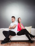 Young couple after quarrel sitting on sofa back to back Stock Image