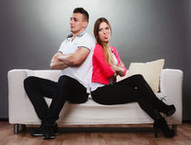 Young couple after quarrel sitting on sofa back to back Stock Images