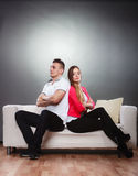 Young couple after quarrel sitting on sofa back to back Stock Photos