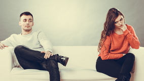 Young couple after quarrel sitting on sofa. Bad relationship concept. Man and women in disagreement. Young couple after quarrel sitting on sofa Royalty Free Stock Photos