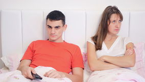 Young couple quarrel because of tv. The unhappy young woman and her joyful husband watching TV lie in bed. The family conflict stock video