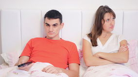 Young couple quarrel because of tv. The unhappy young woman and her joyful husband watching TV lie in bed. The family conflict stock footage