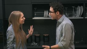 Young couple quarreling in the kitchen. Man and woman scream at each other in frustration stock footage