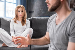 Young couple quarreling. Upset young couple quarreling and gesturing at home Royalty Free Stock Images