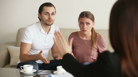 Young couple quarrelling at psychoanalyst office. Family facing relationship difficulties. Young couple visiting professional psychotherapist office, fighting stock footage