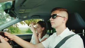 A young couple quarrels in the car, have an unpleasant conversation. Problems of a young family