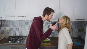 Young couple quarrels in the kitchen. Man and woman scream in frustration and angrily gesticulate stock video footage